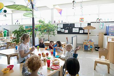 Preschool teacher and students eating during snack time in classroom - p1192m1560200 by Hero Images