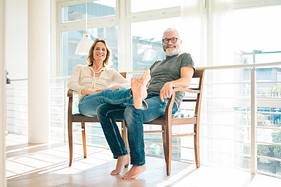 Portrait of relaxed mature couple sitting on chairs at home - p300m1568313 von Robijn Page