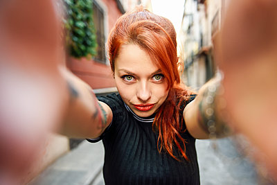 Selfie portrait of red-haired woman in the city - p300m2132042 von Javier Sánchez Mingorance