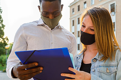 Male and female university students wearing protective face mask while discussing in campus - p300m2226553 by Ignacio Ferrándiz Roig