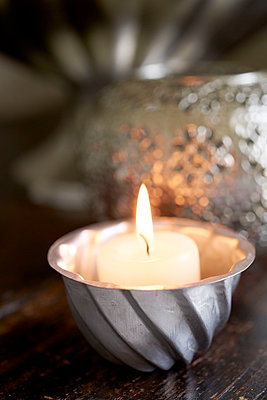 Single lit candle in metal bowl - p349m2167799 by Polly Wreford