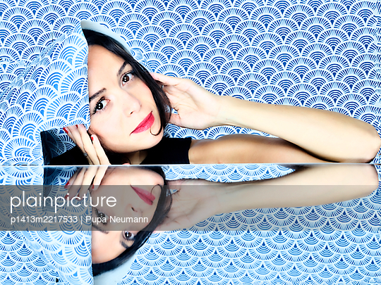 Mirror image of a young woman with wallpaper, portrait - p1413m2217533 by Pupa Neumann