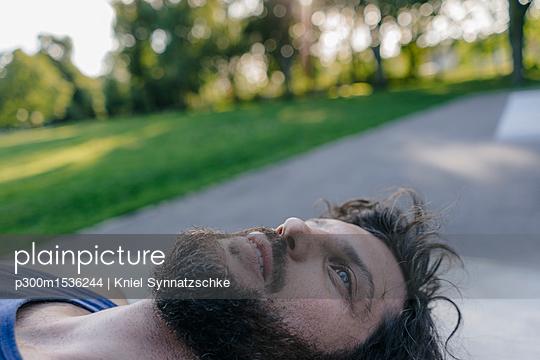 plainpicture | Photo library for authentic images - plainpicture p300m1536244 - Relaxed man lying in skatepark - plainpicture/Westend61/Kniel Synnatzschke