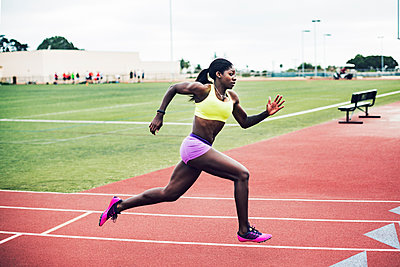 Side view of determined female athlete running on tracks - p1166m1086172f by John Trice