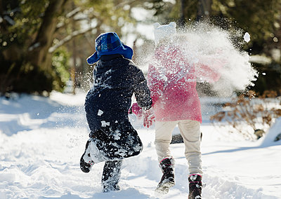 Two children running in snow - p1427m2283142 by Roberto Westbrook