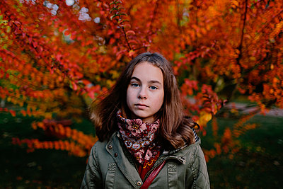 Portrait of young girl in a park, autumn tree in the background - p300m2121844 von Oxana Guryanova
