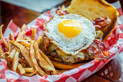 Basket of french fries with cheeseburger and egg - p555m1464381 by Inti St Clair photography
