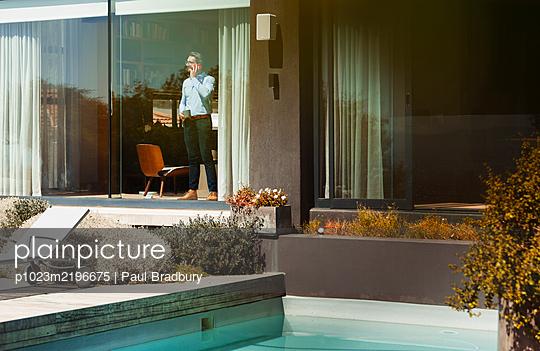 Businessman talking on smart phone at sunny, modern patio window - p1023m2196675 by Paul Bradbury