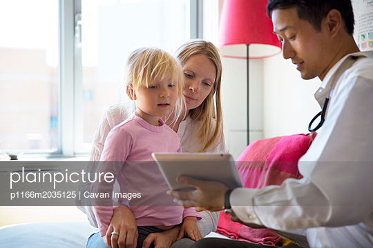 Doctor showing tablet computer to family - p1166m2035125 by Cavan Images
