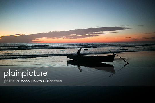 Fisherman returns to beach at sunset - p919m2108335 by Beowulf Sheehan
