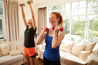 Happy preteen girl friends exercising with dumbbells in living room - p1023m2238508 by Himalayan Pics