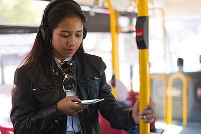 Teenage girl using mobile phone in the bus - p1315m1565927 by Wavebreak