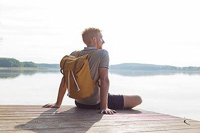 Junger Mann sitzt auf Steg am See - p1396m1496716 von Hartmann + Beese