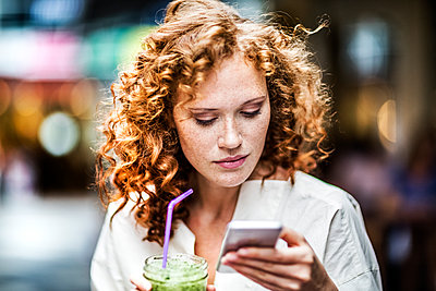 Portrait of young woman with beverage looking at cell phone - p300m1505379 by Jo Kirchherr