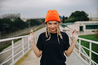 Smiling young woman holding braided hair while standing on footbridge against sky - p300m2242232 by Aitor Carrera Porté