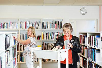 Women choosing books in library - p312m2237465 by Phia Bergdahl