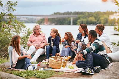 Family and friends looking at senior woman while sitting on lakeshore in park - p426m2074343 by Maskot