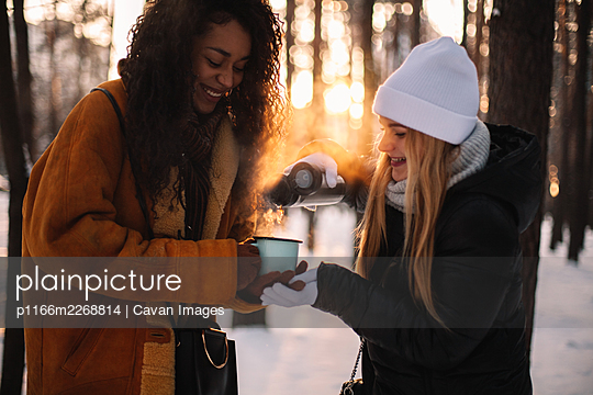 Happy woman pouring tea for girlfriend standing at park during winter - p1166m2268814 by Cavan Images