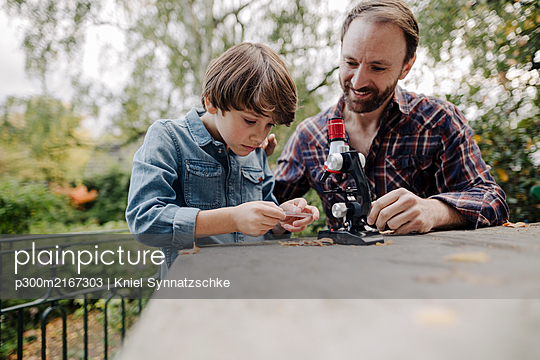 Father and son looking at objects under a microscope - p300m2167303 by Kniel Synnatzschke