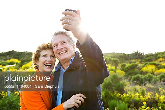 Caucasian couple taking picture outdoors - p555m1464084 by Sam Diephuis
