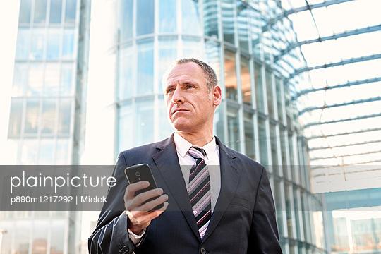 Geschäftsmann mit Handy - p890m1217292 von Mielek