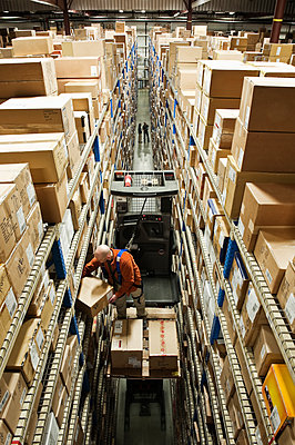 Looking down on an employee picking a box out of a rack, while standing on a motorized stock picker in a distribution warehouse. - p1100m2002272 by Mint Images