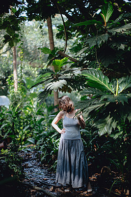 Woman standing in tropical forest - p1414m1590572 by Dasha Pears