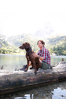 Austria, Tyrol, woman with dog sitting on tree trunk at lake Seebensee - p300m2083380 by Florian Küttler