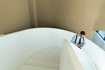 Businessman using cell phone on stairs in modern office - p300m2102360 by Hernandez and Sorokina