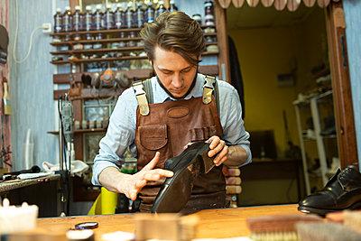 Male cobbler examining shoe at workshop - p300m2282854 by Vladimir Godnik