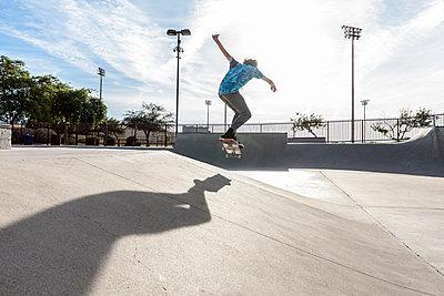 Hispanic man performing mid-air trick on skateboard - p555m1444126 by Kolostock