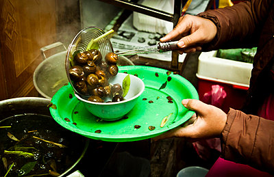 Snails being served at a food stall in Hanoi, Vietnam, Asia - p934m832427 by Dominic Blewett
