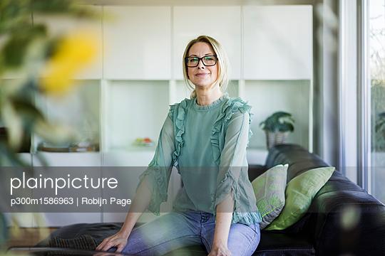 Portrait of content businesswoman sitting on couch - p300m1586963 von Robijn Page