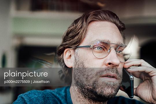 Male entrepreneur talking on smart phone in cafe - p300m2275509 by Joseffson