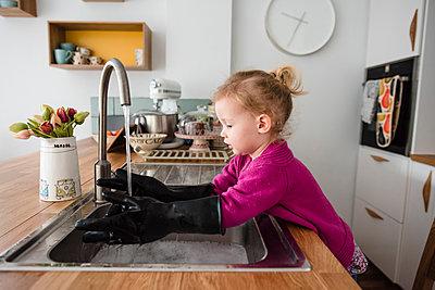 Girl wearing gloves washing hands in kitchen sink - p1166m1211553 by Cavan Images