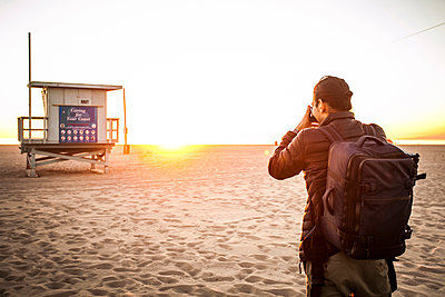 Rear view of backpacker photographing lifeguard hut with camera at beach during sunset - p1166m1556350 by Cavan Images