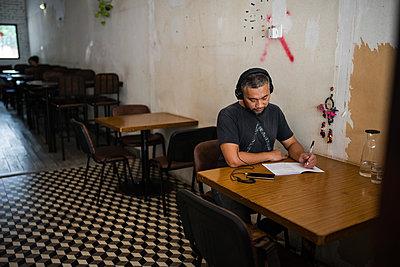 Asian man listening music on headphones - p1166m2131275 by Cavan Images