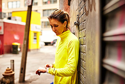 A woman setting her fitness watch on a city street - p1166m2212038 by Josh Campbell