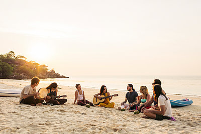 Thailand, Koh Phangan, group of people sitting on a beach with guitar at sunset - p300m1568328 by Mosuno Media