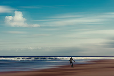 France, uvelle-Aquitaine, Contis, Clouds over hooded man standing on Contis Plage beach - p300m2198018 by Dirk Wüstenhagen