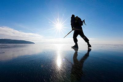 Man ice-skating of frozen lake - p575m696339f by Henrik Trygg