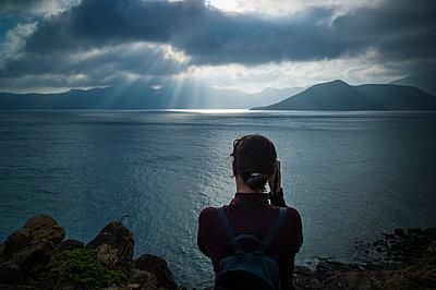 A woman takes pictures of a peaceful seascape in Con Dao, Ba Ria  Vung Tau Province, Vietnam - p934m1451251 by Sebastien Loffler