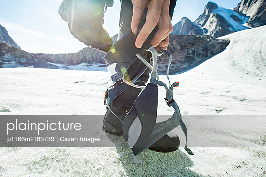 Detailed low angle view of climber stepping into climbing harness. - p1166m2189739 by Cavan Images