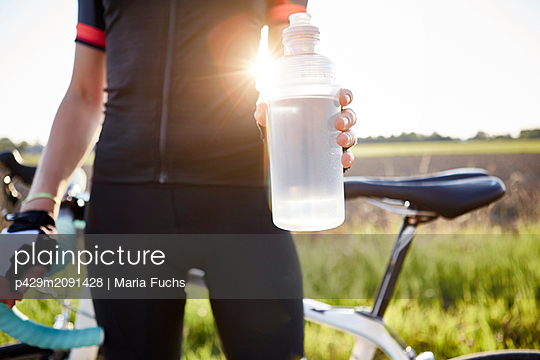 Female cyclist holding water bottle, mid section - p429m2091428 by Maria Fuchs