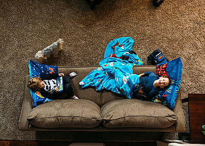 Overhead view of boys lying on sofa at home - p1166m1174172 by Cavan Images