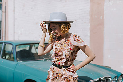 Woman wearing hat by vintage car - p429m1569675 by Lena Mirisola