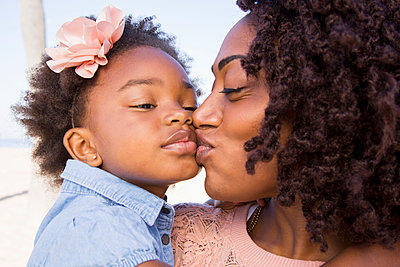 Close up of black woman kissing daughter - p555m1523170 by Ronnie Kaufman