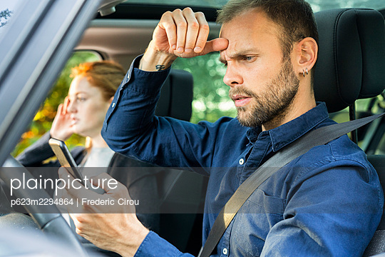 Frustrated young man using smart phone while driving a car - p623m2294864 by Frederic Cirou