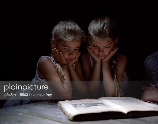 Zwei Mädchen lesen ein Märchenbuch - p945m1155031 von aurelia frey