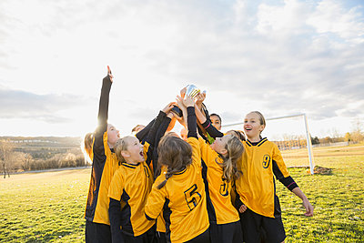 Girls soccer team celebrating with trophy - p1192m1043996f by Hero Images